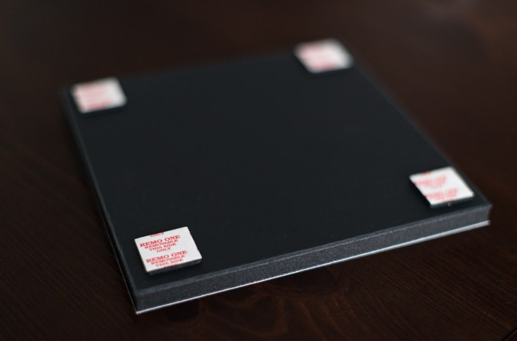 """Attach the provided adhesive squares to the back of the boards 1/2"""" in from the edges."""