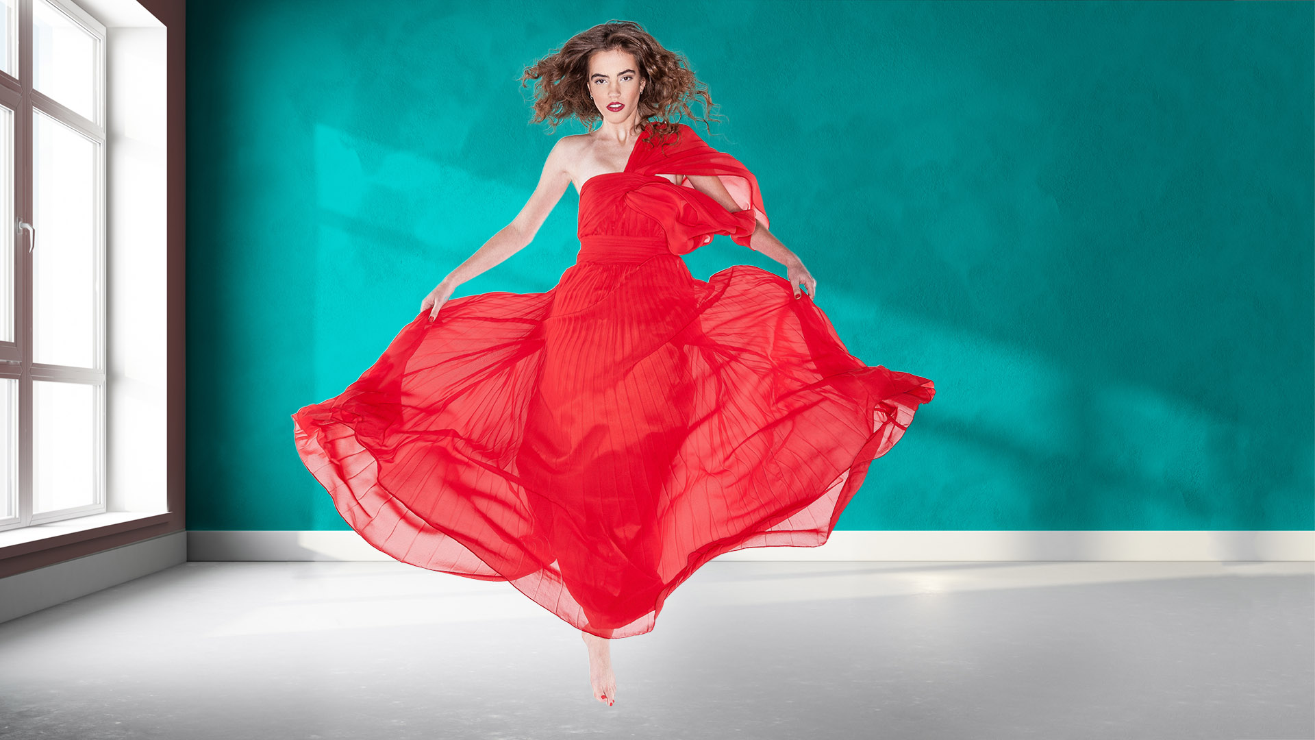 Amy Patterson wearing a red dress jumping in a daylit room with a cyan wall. Amy's photo by Kevin Ames