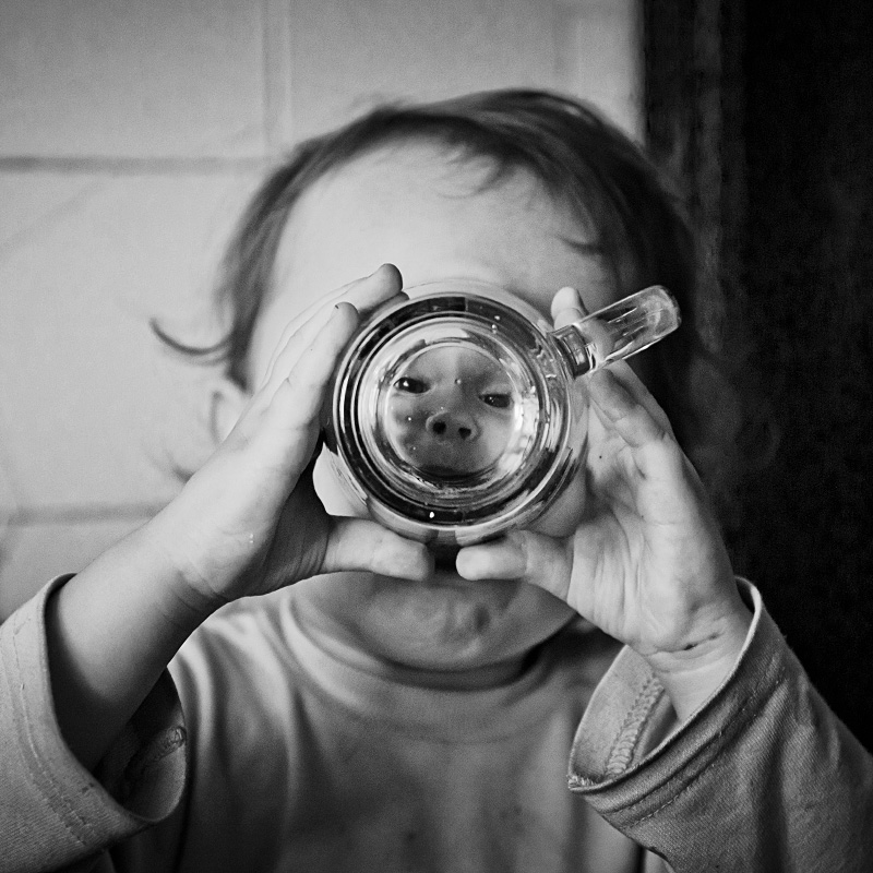 A baby peers through the bottom of a clear glass mug that distorts his face.