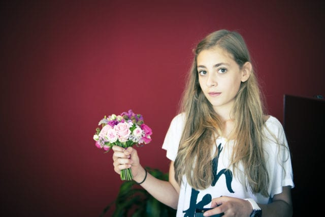 girl, flowers, bouquet, red, red wall, blonde, long hair, teenager