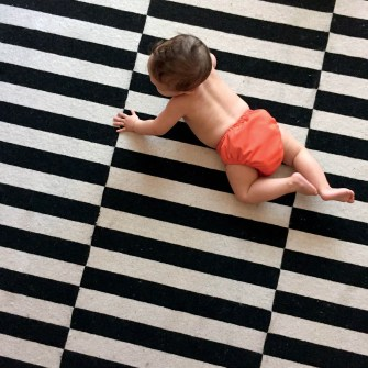 The striking pattern of the rug broken by a baby.