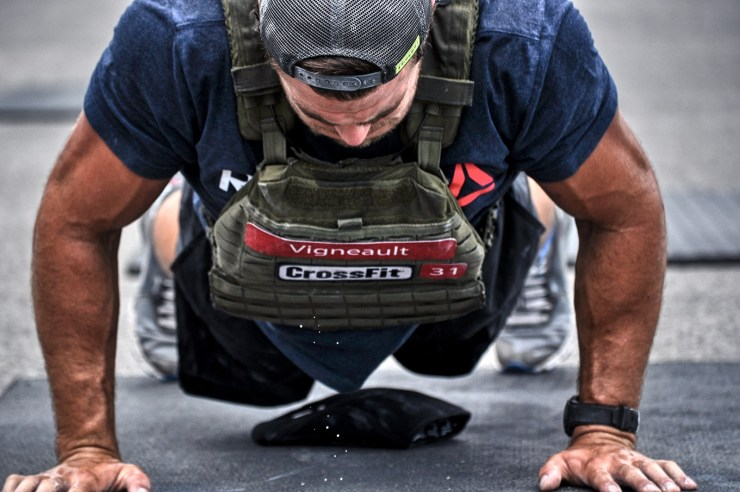 CrossFit Games athlete Alex Vigneault dripping sweat doing a push up during Murph workout