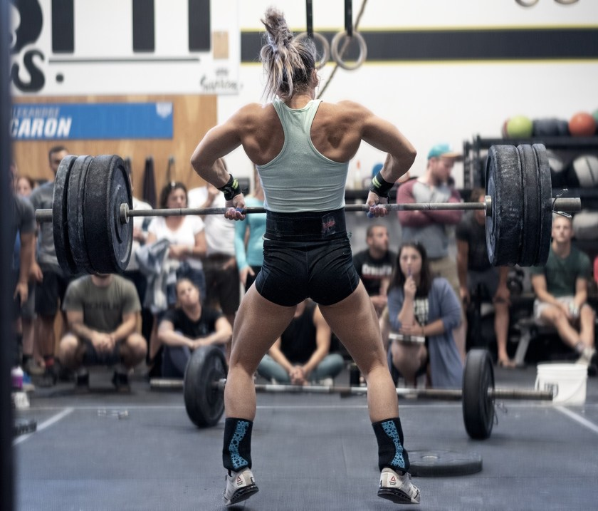 CrossFit athlete Jessica Cote-Beaudoin does a heavy clean and jerk in front of a crowd.