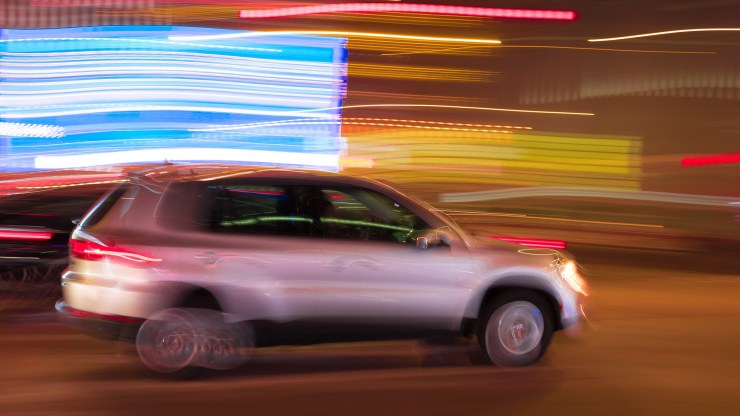 Slow shutter speed lets the car blur against a streaked background of light.