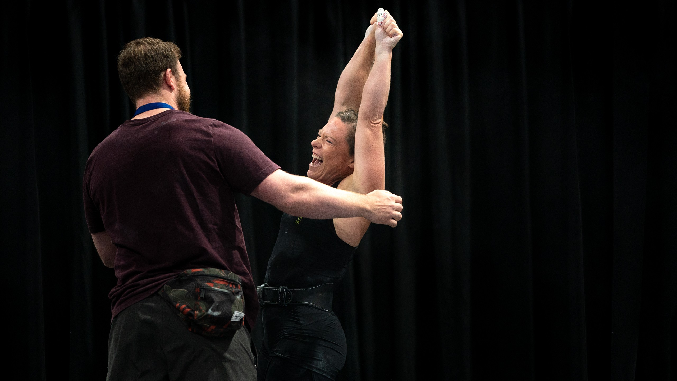 Femalt weightlifter celebrates hands in the air with her coach after winning the championship