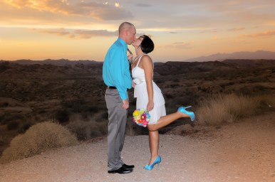 Photographers of Las Vegas - Wedding Photography - wedding couple at valley of fire sunset bride grabbing grooms tie