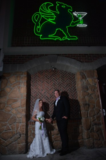 Photographers of Las Vegas - Wedding Photography - wedding bride and groom standing in front of Griffin neon sign