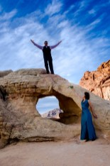 Photographers of Las Vegas - Wedding Photography - wedding couple climbing arch at valley of fire