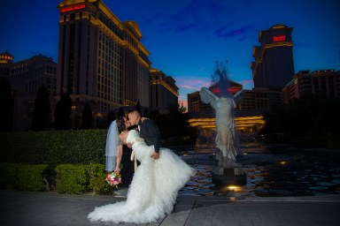 Photographers of Las Vegas - Wedding Photography - wedding couple groom dips and kisses the bride at sunset Ceasars Palace