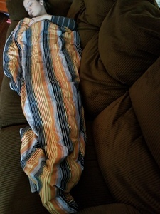 Image shows a woman lying on a couch under a weighted blanket