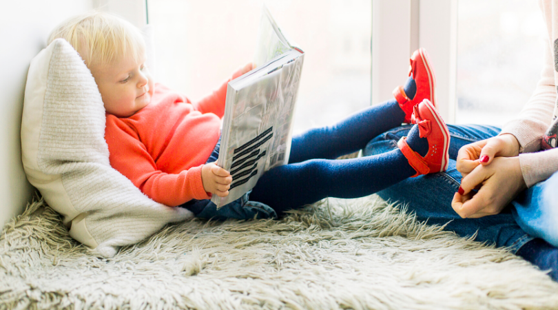 Picture of a little girl looking at a large book while reclining with her mom.