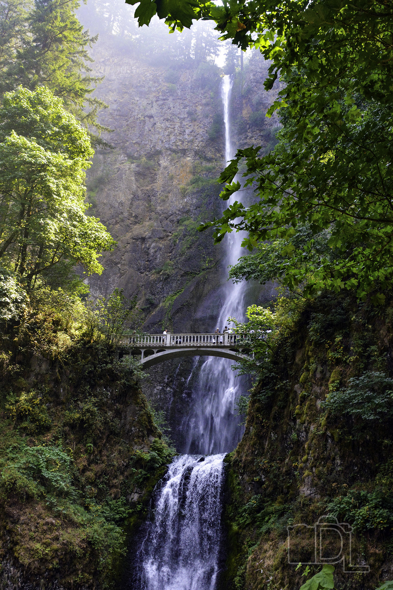 The Multnomah Falls waterfall in Oregon's Columbia River Gorge pours down 611 feet past a walking bridge of tourists.