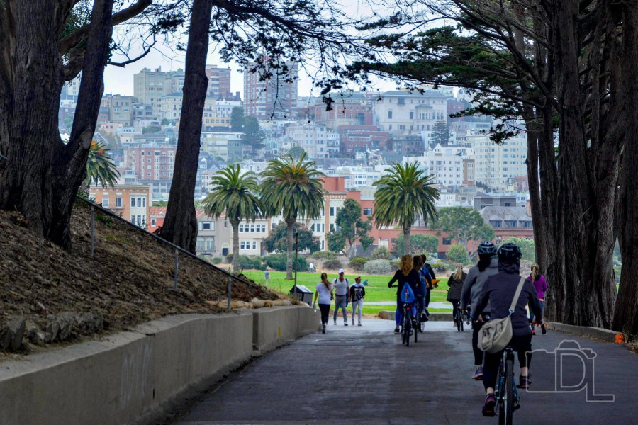 Bicyclists enjoy a framed view of San Francisco's Marina-Cow Hollow neighborhoods from atop a steep hill at Fort Mason.