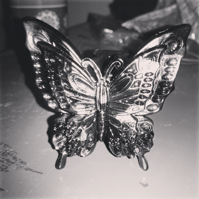 a black&white photo of a hair clip shaped like a butterfly