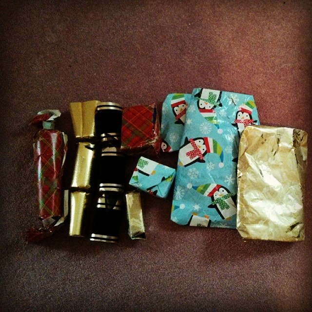 a photo of some christmas presents and christmas crackers on a carpet