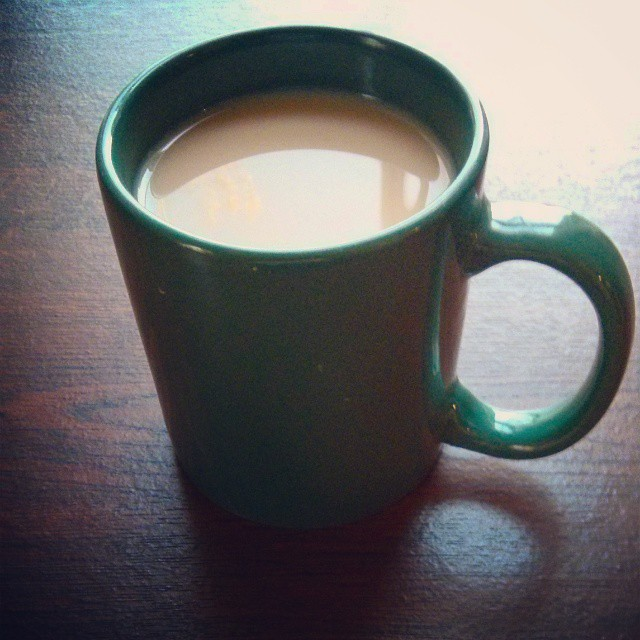 a photo of a green mug full of tea