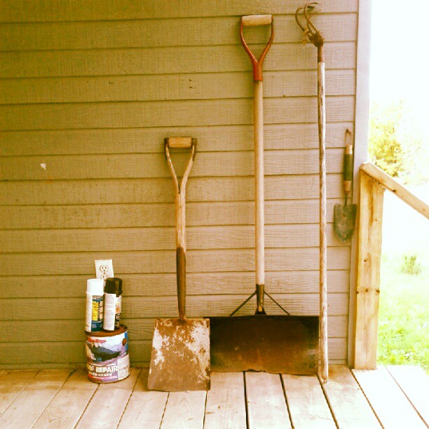 a photo of some paint cans and yard tools on a deck