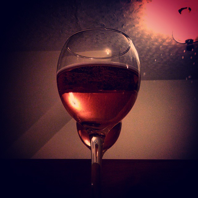 a dark photo of a glass fill with rose wine