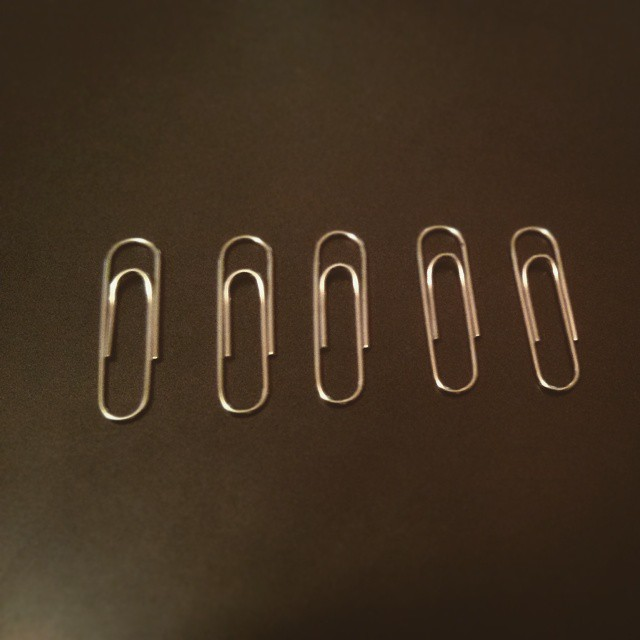 a photo of five silver paper clips close up