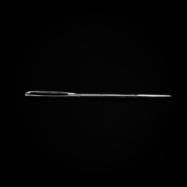 a macro photo of a sewing needle