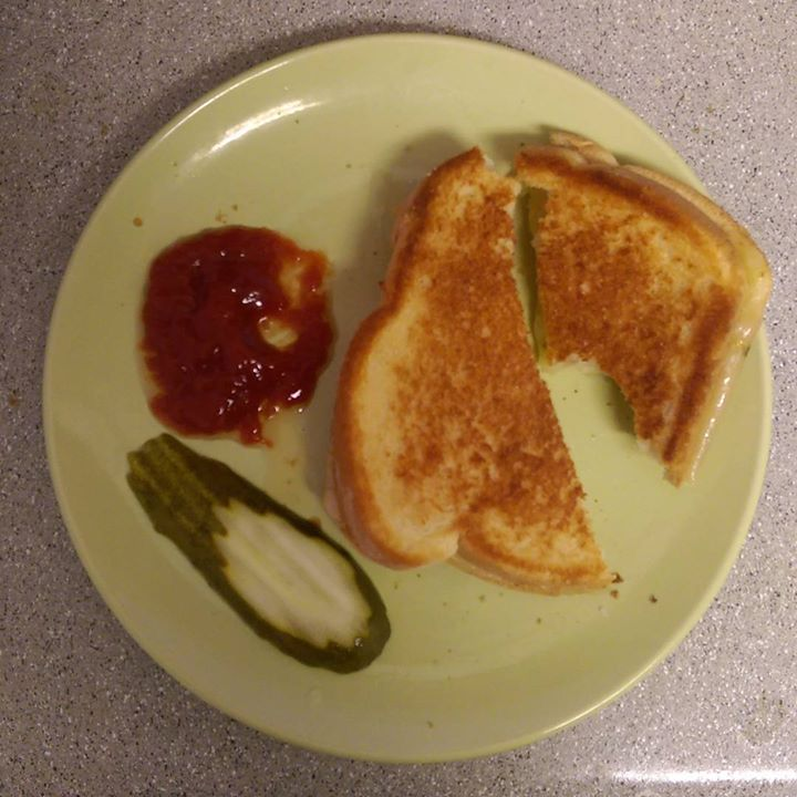 a photo of a grilled cheese on plate with a pickle and some ketchup