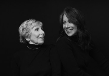 Black and white portrait of an elderly woman with her adult daughter smiling at each other