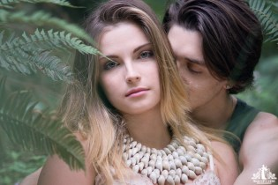 Natural light portrait of a young couple cuddling in a wooded area surrounded by ferns