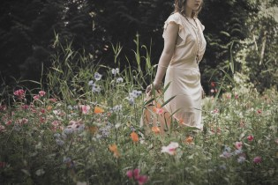Natural light portrait of a young woman in a vintage slip dress walking through a field of wild flowers