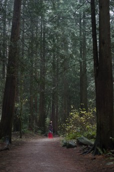 Natural light portrait of a young woman in a red dress and flower crown standing between the trees in Pacific Spirit National Park