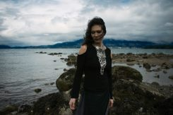 Outdoor natural light portrait of a woman on a rocky shoreline with moody cloudy skies and the wind blowing her curls into her face