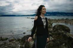 Outdoor natural light portrait of a woman on a rocky shoreline wearing a larger silver breastplate necklace standing facing the wind as it blows her hair away from her face