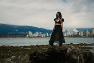 Outdoor natural light portrait of a woman standing on a washed up log on a rocky shoreline looking out to sea with English Bay in the background