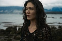 Outdoor natural light portrait of a woman standing on a rocky shoreline with moody skies looking out over the water with her face framed by curls
