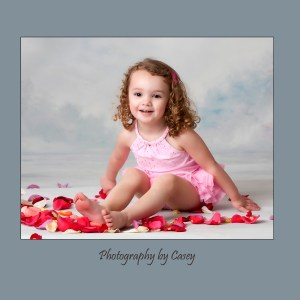Photographer of little girls playing in rose petals