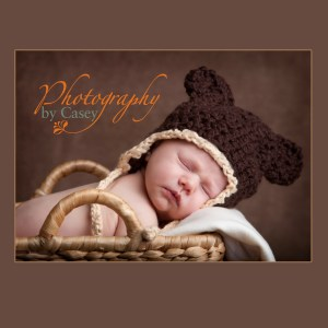 newborn baby sleeping in basket with teddy bear cap photographer