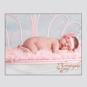 sleeping newborn baby on pink bench