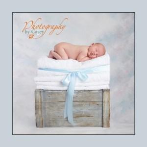 Stask of towels holding sleeping newborn baby