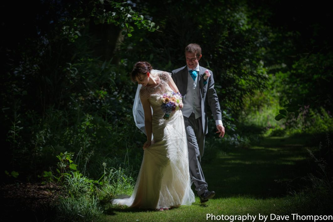 The bride and groom walk in teh grounds at Combermere Abbey