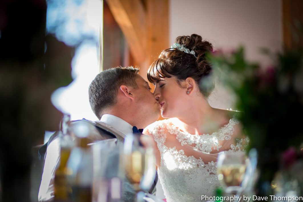 The bride and groom share a kiss during the wedding breakfast