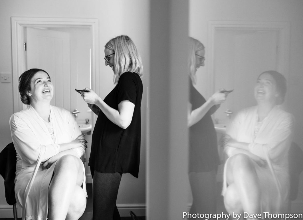 The bride is reflected in a fridge door during bridal prep