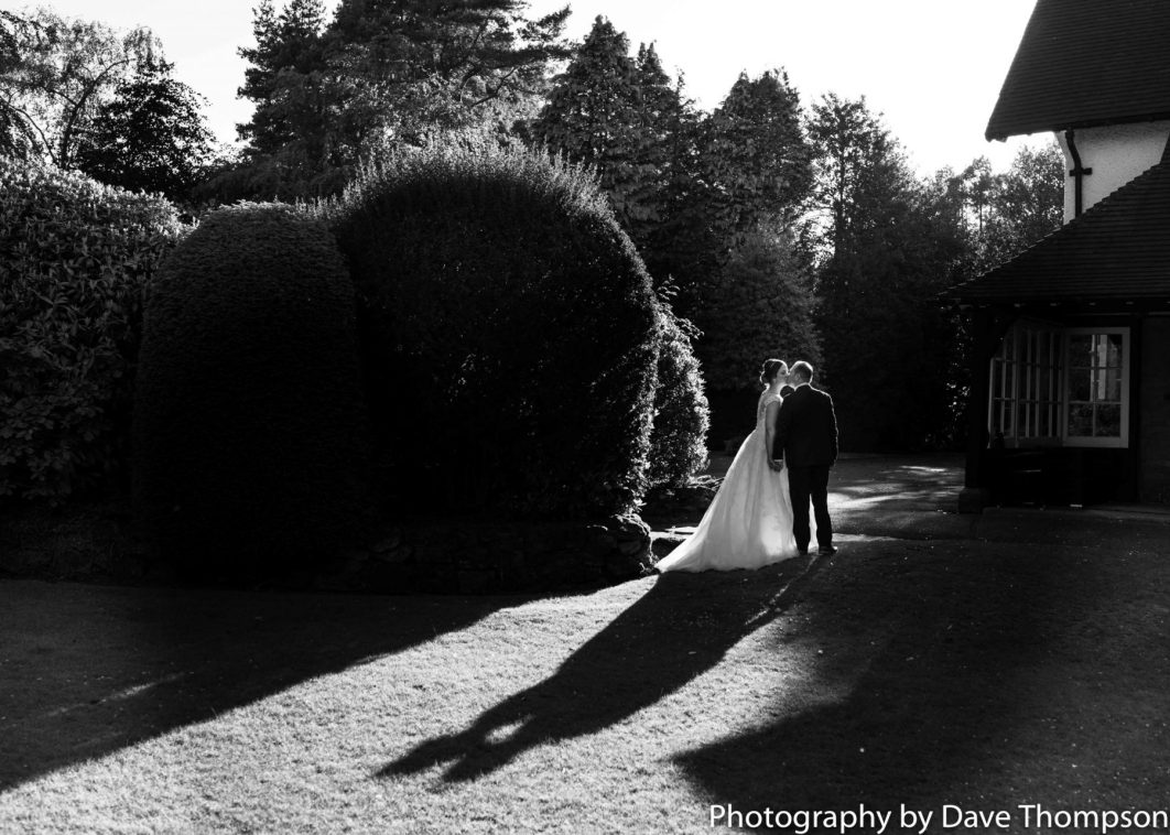 A black and white photograph of the bride and groom and shows cast by evening sunshine