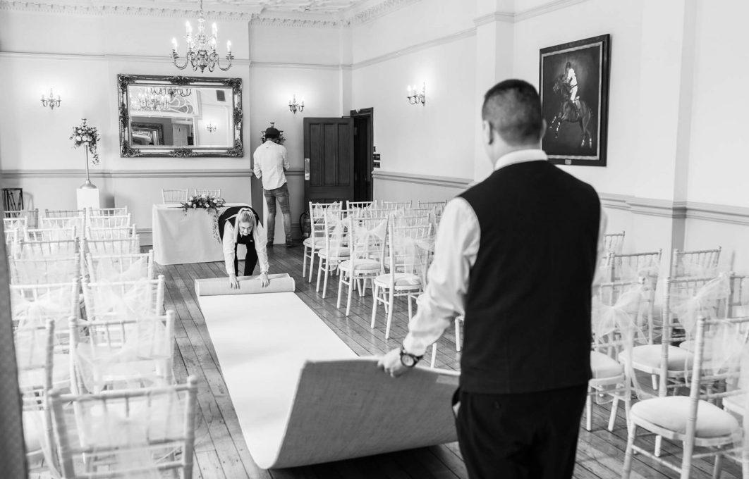 Staff at Nunsmere Hall prepare the wedding ceremony room