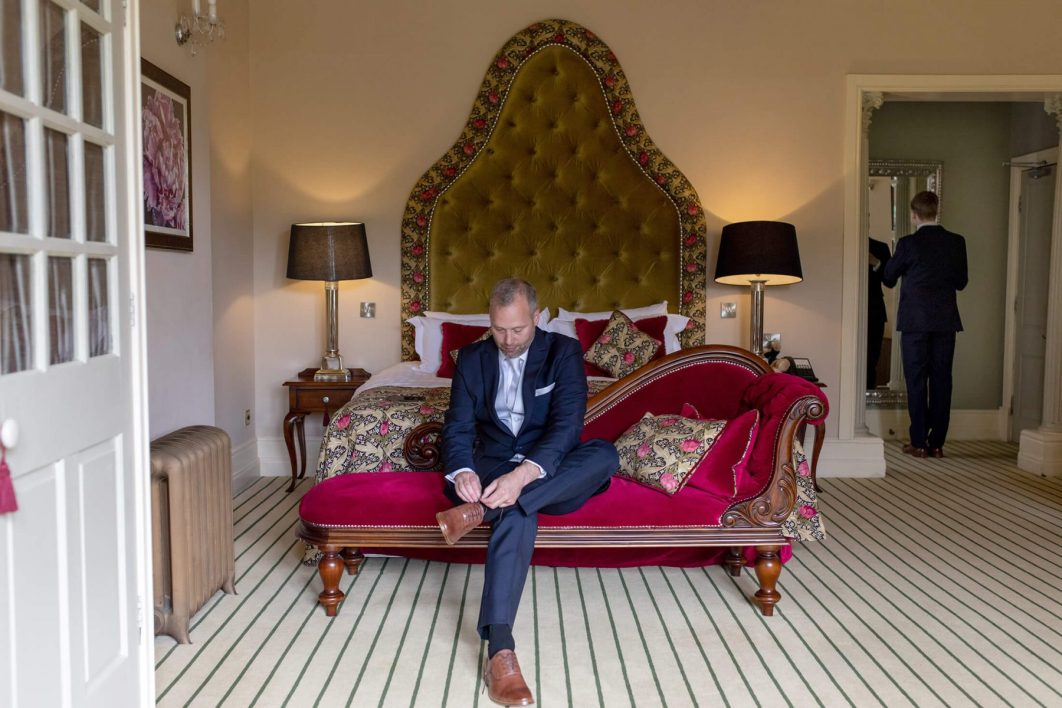 The groom ties his laces in the bridal suite at Nunsmere Hall in Cheshire.