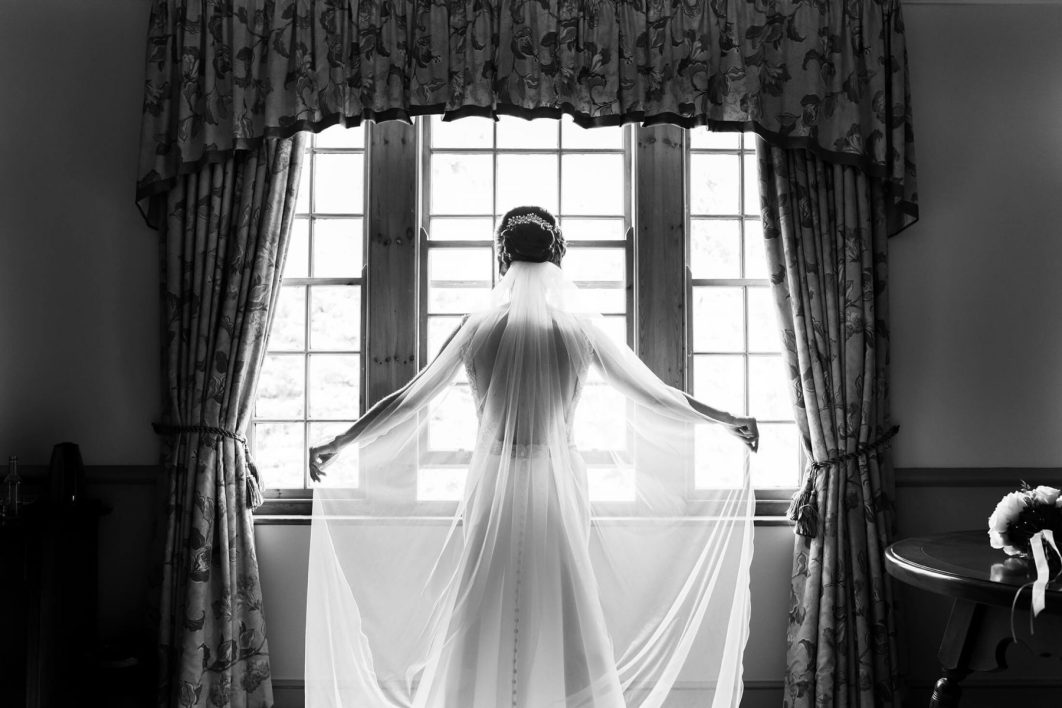 The bride holds her veil in front of a large window.