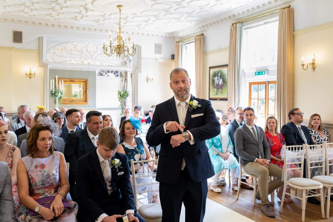A groom points to his watch as the bride arrives late.