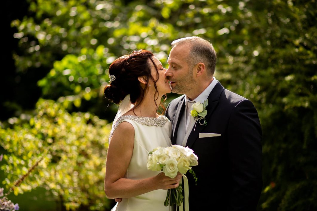The bride and groom share a kiss after their wedding.
