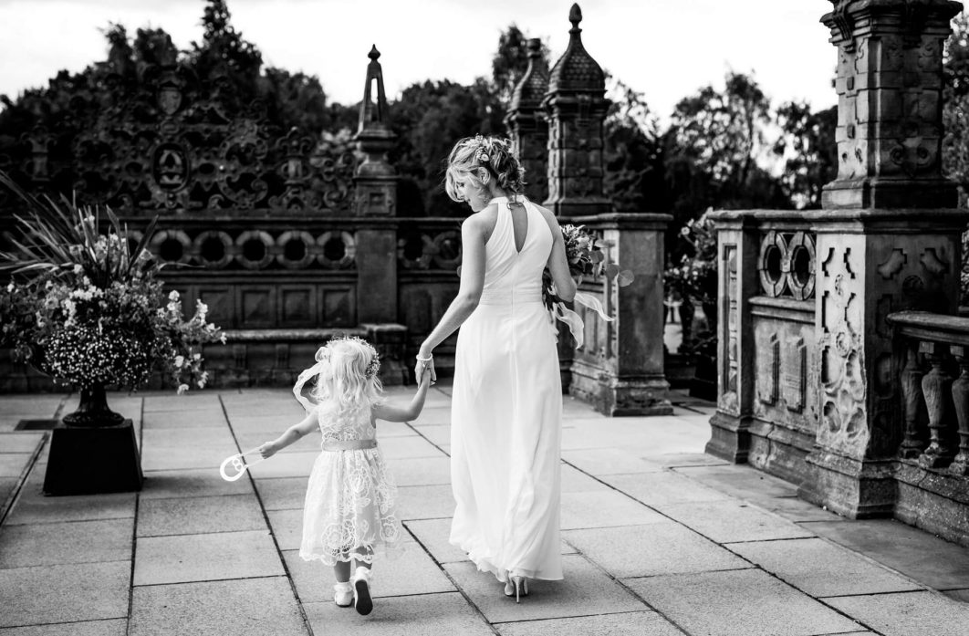 Natural wedding photography The bride holds hands with her daughter as she leaves Crewe Hall after geting ready for her wedding. Crewe Hall Wedding Photographer