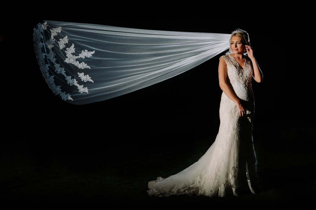 A night time protrait of a bride and her stunning veil blowing in the wind. Wychwood Park wedding photographer