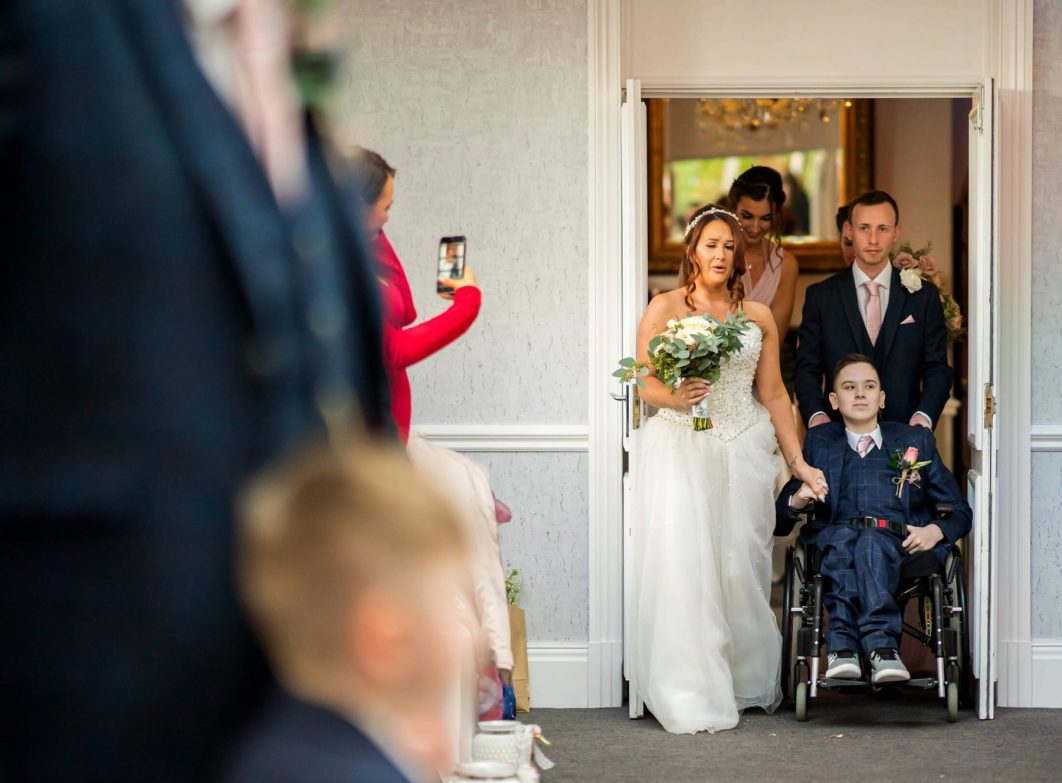 Hollin Hall Hotel Wedding Photographer - The bride is led down the aisle by her son in his wheelchair.