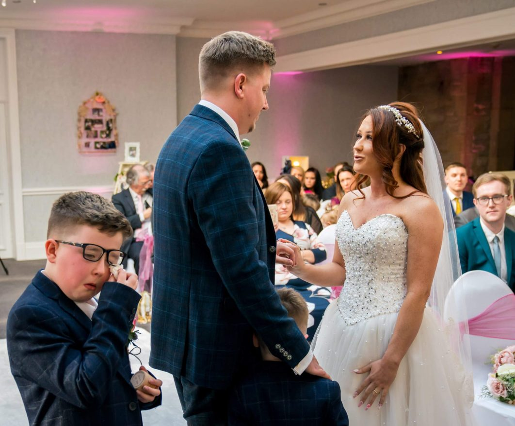 Hollin Hall Hotel Wedding Photographer - The bride and groomduring the ceremony as one of thier sons wipes his eye